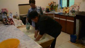 Leonilde Valente prepara o pão com a ajuda de Maria Isabel